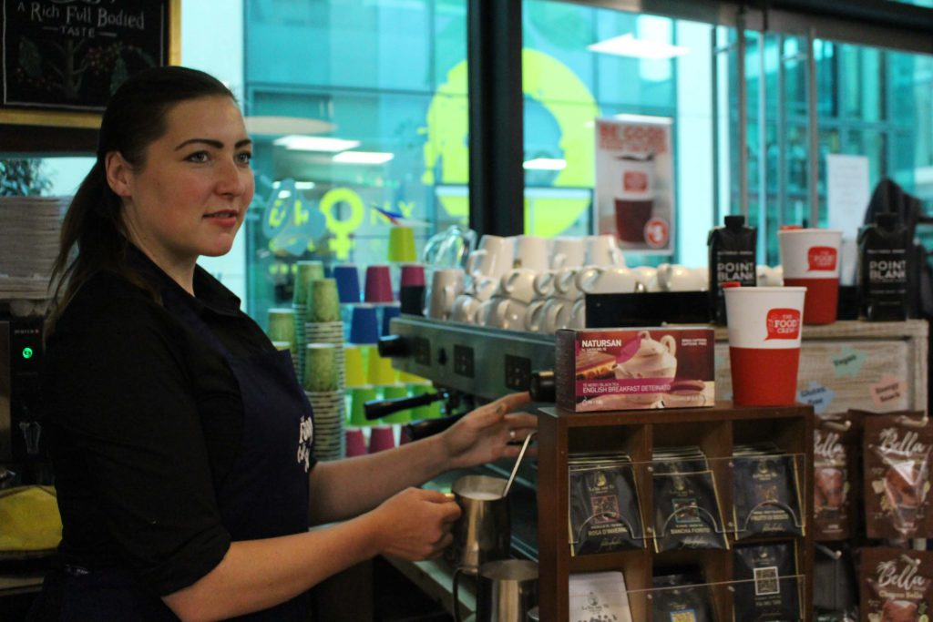 the food crew cafe in sandyford showing female barista making a coffee behind the counter