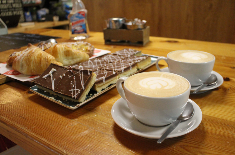 tea coffe and cake in sandyford two cups of coffee on a wooden surface beside a plate of cake and biscuits